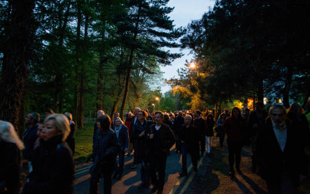 A large crowd walking through a wooded area at dusk.