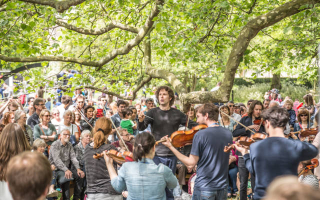 An orchestra perform outside, under a large tree. Lots of people are watching them. It is a sunny day.