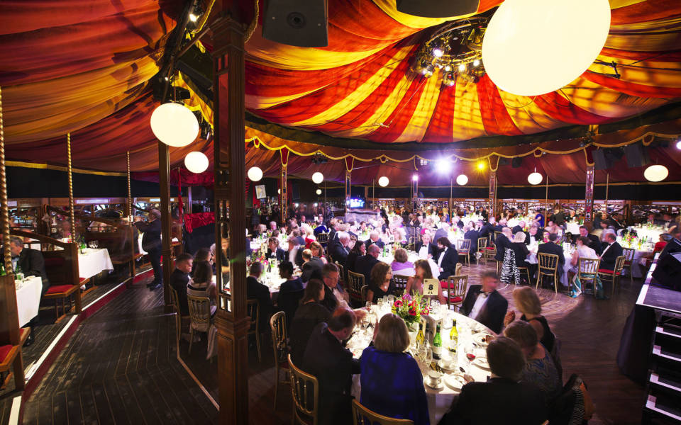 Picture from the NNF17 Gala, inside the Adnams Spiegeltent. People sit around circular tables.