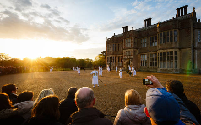 Image from Wolf's Child, a 2015 Festival show. Audience members stand in a semi-circle, watching women wearing long white dresses. Felbrigg Hall is in the right side of the picture.