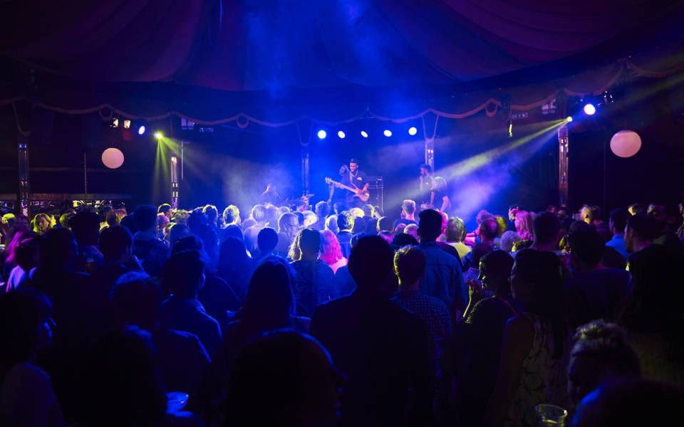Picture taken inside the Adnams Spiegeltent. A five piece jazz band 'Ezra Collective' are on stage, a busy crowd, illuminated in blue light, is watching them.