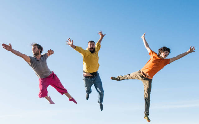 Three men jump high in the air.