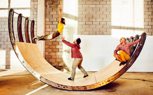 Three people are doing acrobatics inside a huge wooden seesaw.