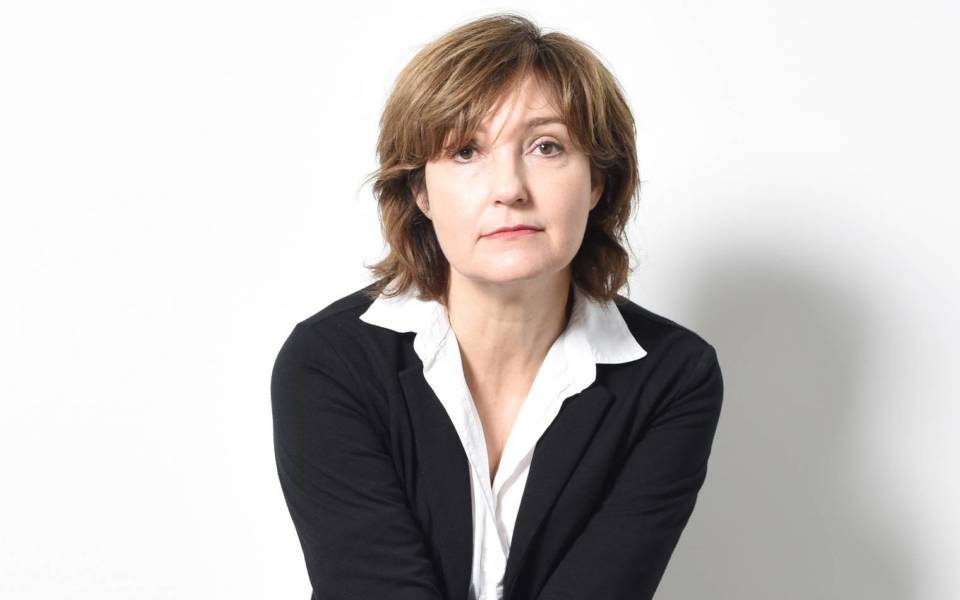 Viv Albertine, wearing a white shirt and black suit jacket.