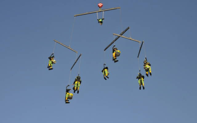 Drummers suspended by crane forming a mobile