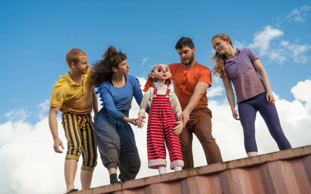 Four people stand on top of a shipping container, they are looking at a small puppet.