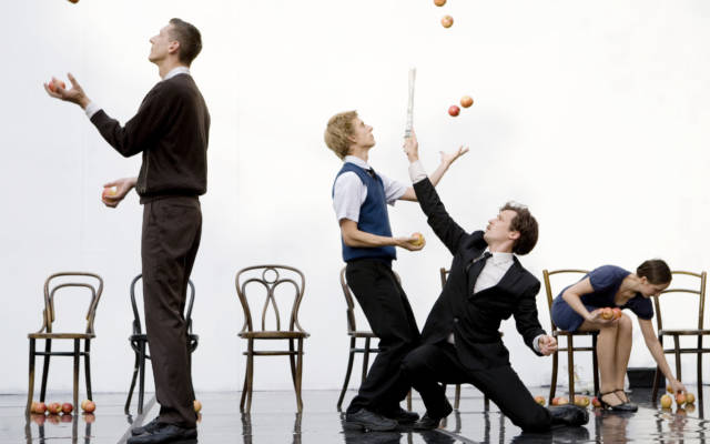 Two men stand back to back juggling apples, whilst a women sits down holding apples and man strikes a pose with a newspaper.