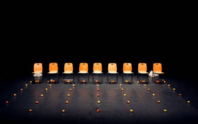 A row of empty chairs with rows of apples in front of them