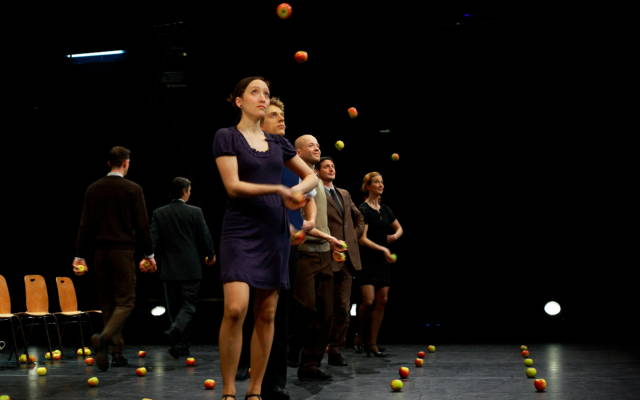 A group of men and women stand in a row juggling apples