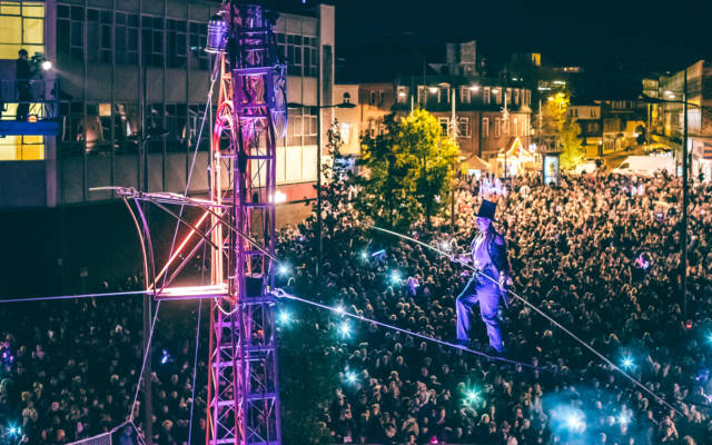 Chris Bullzini tight-rope walking at night, above a big crowd, illuminated by purple lights