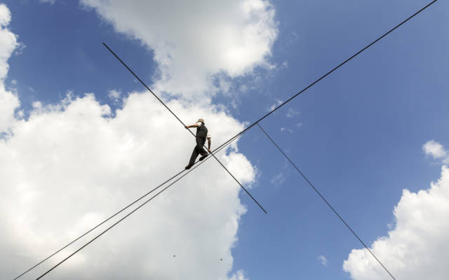 A man walks across a high tight-rope