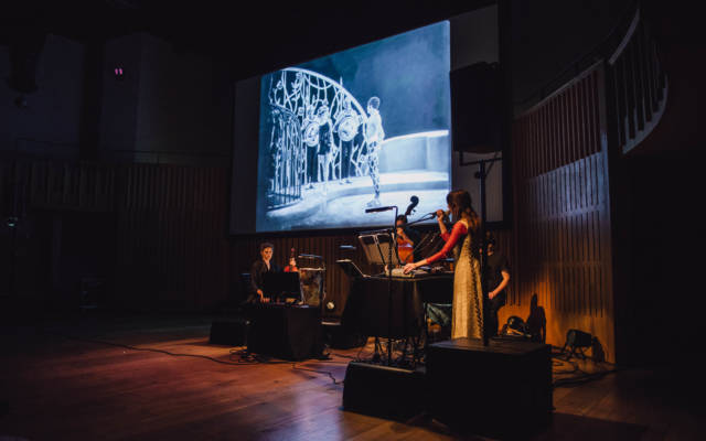 Haley Fohr and band perform in front of a projection of Salomé