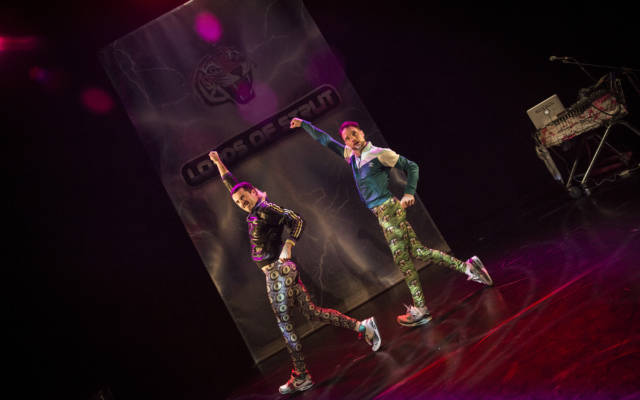 Two men wearing bright lycra trousers and sports jacks dance in sync