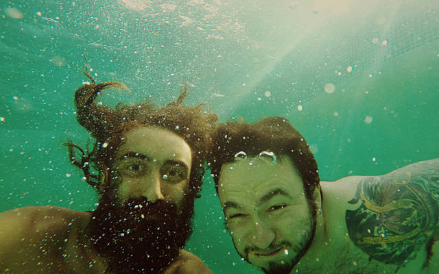 Photo: two men underwater, surrounded by bubbles, smiling to the camera