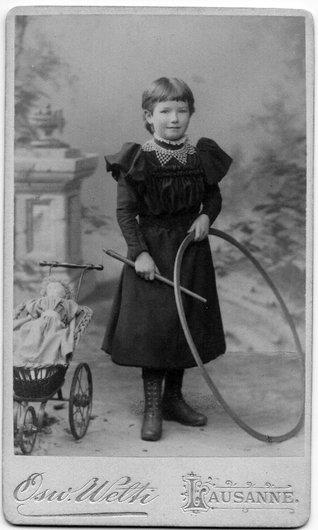 Petite fille, cerceau, landau et poupée