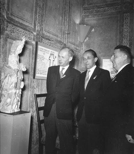 Trois hommes posent à côté de la statue médiévale de Sainte Catherine, sculptée par Guillaume de Calesio