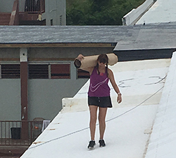 Ayesha volunteers - walking across roofs with equipment
