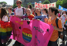 Four people at durham pride wearing bright colours and carrying a banner in front of the cathedral