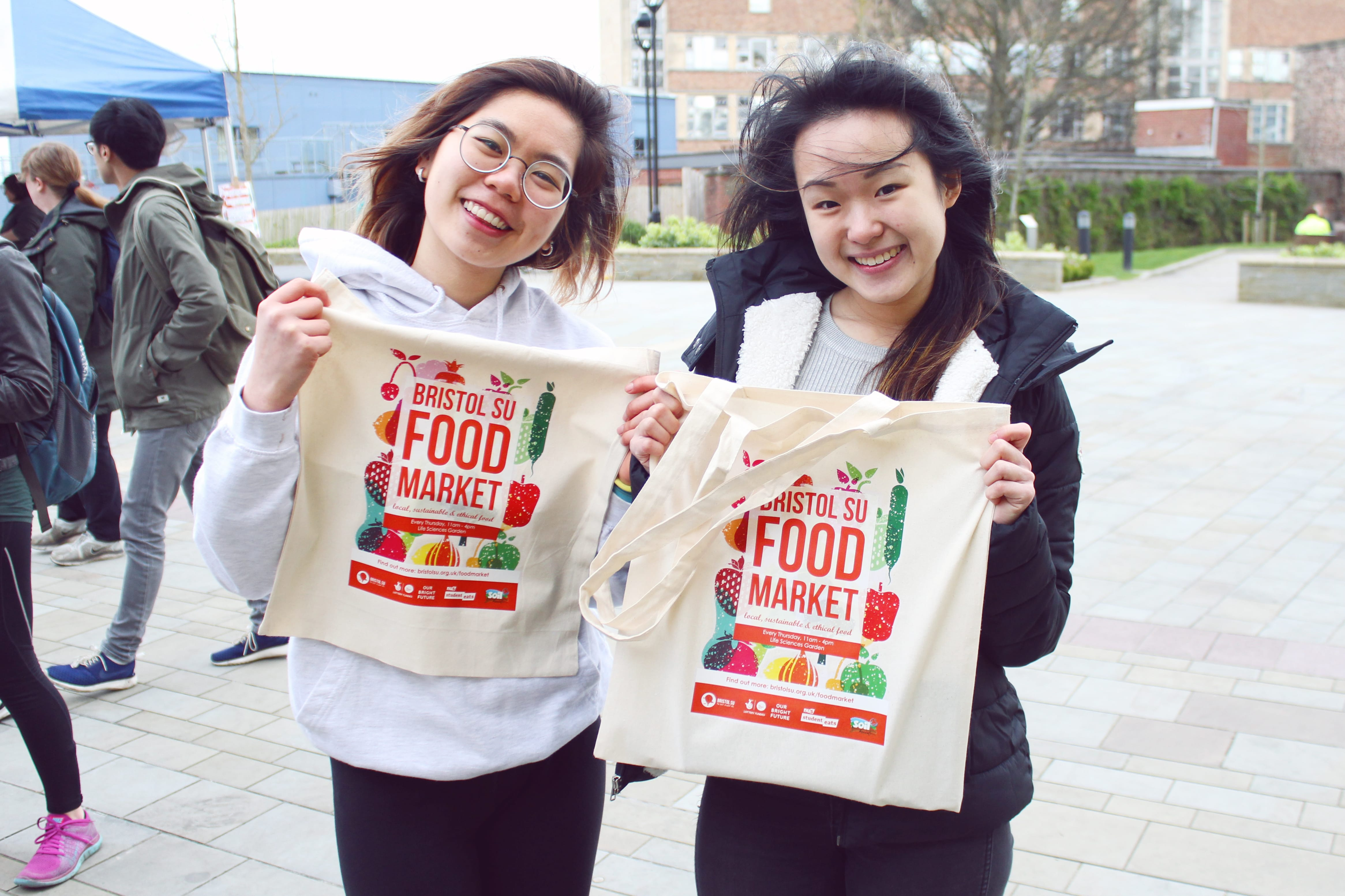 Two students sporting cotton tote bags