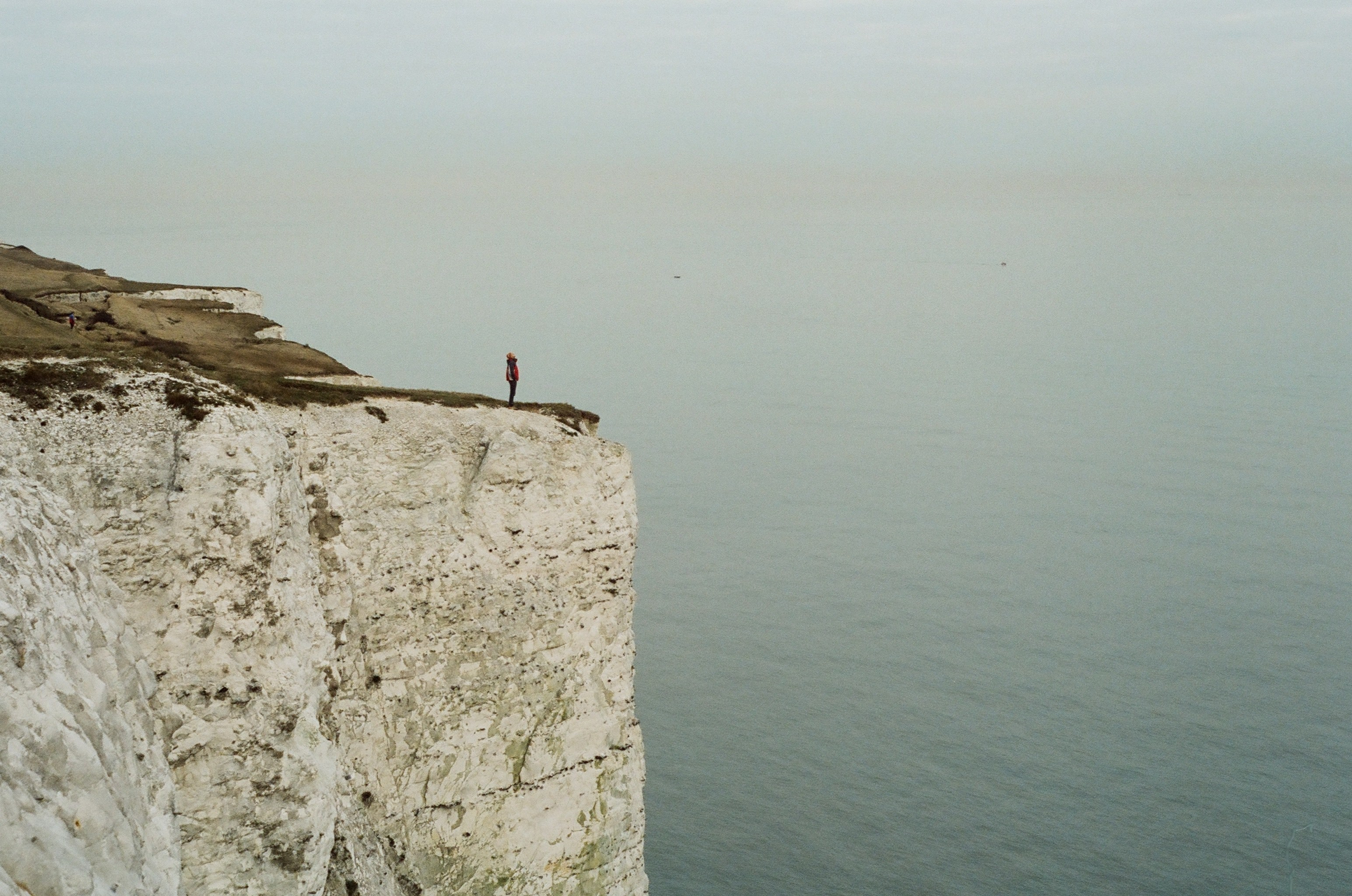 Long distance shot of a figure standing on the edge of a cliff.