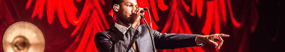 Leon Bridges pointing out at the audience whilst performing at The Anson Rooms. He plays in front of a hanging red velvet curtain