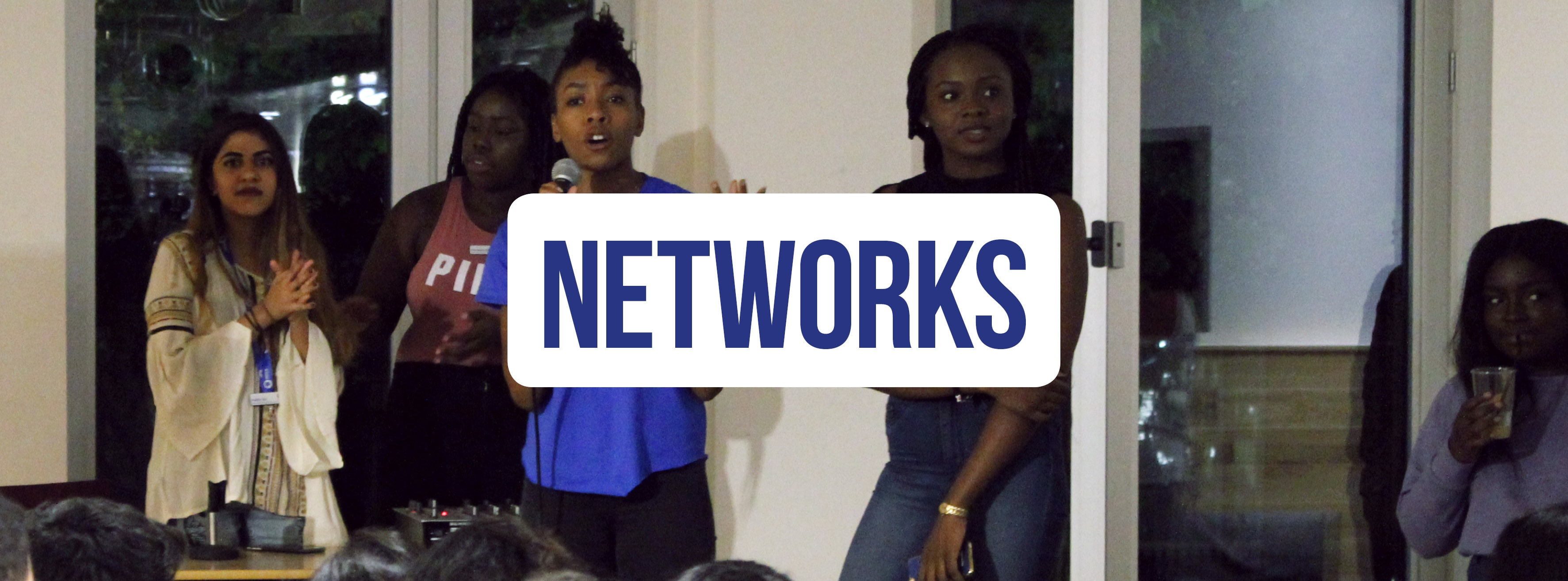 Banner with the word 'networks' with students making a speech in the background