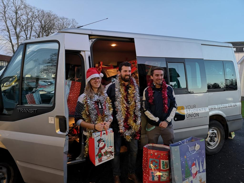 Sabbatical Officers Becky, Josh and Rob are smiling outside an SU van full of presents