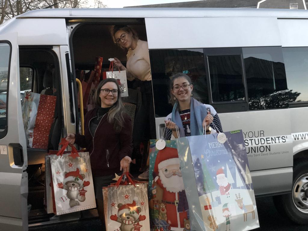 The SU Team are standing in front of the SU van with presents donated to the MR Appeal