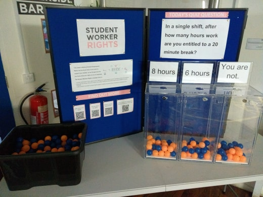 Stall which has information about student worker rights and a quiz question with balls to vote with.