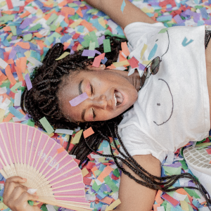 Black woman with braid lying on a pile of rainbow confettis holding a fan