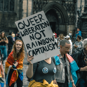 "Pride March with a person holding a sign saying ""Queer liberation not rainbow capitalism"""