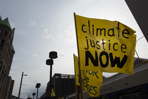 "A flag stating ""climate justice now"" against the background of a sunny sky"