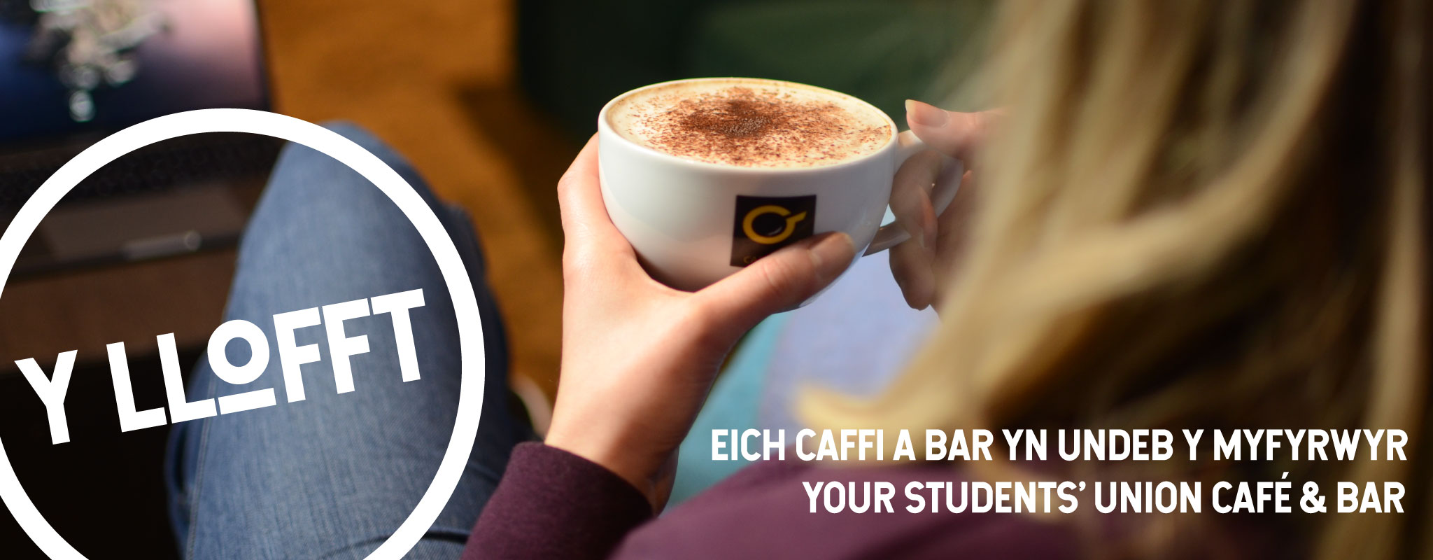 Y Llofft banner. An image of someone enjoying a cup of coffee in the cafe in a large comfy seat.