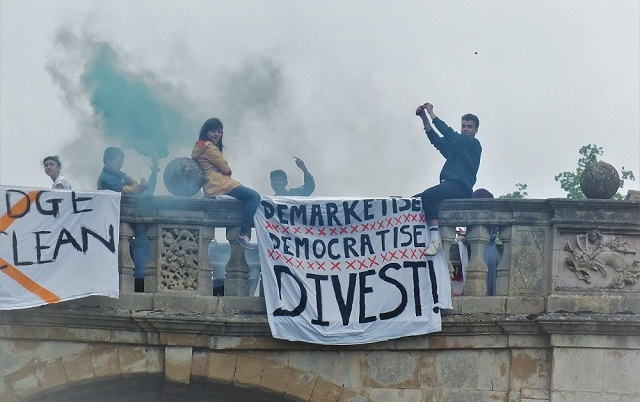 Students protesting on a bridge with banner saying 'Demarketise, Democratise, Divest'