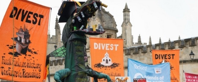 Three big orange banners saying 'Divest' at a protest