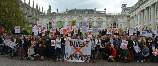 Large group of people cheering and holding posters saying Divest Cambridge