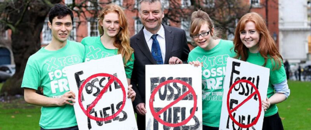 Students stand with Vice Chancellor holding signs with red crosses over the words Fossil Fuel