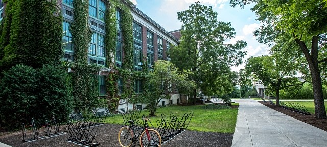 Photo of campus with greenery, bike park and building