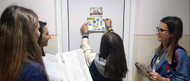 Student volunteers at UoB stick an energy awareness sign on a door