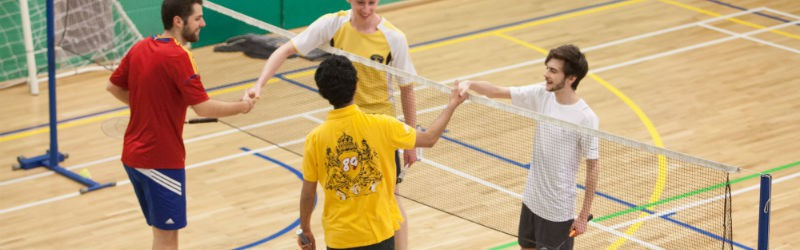 Badminton players shaking hands over badminton net