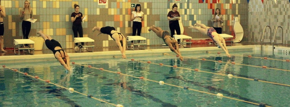 Swimming team diving into pool