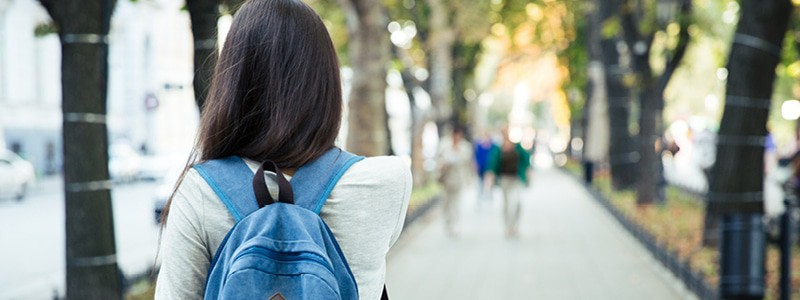 Image of student with dark hair and backpack walking away along a pavement