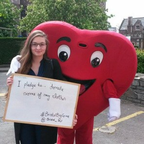 Student standing with mascot dressed as a giant loveheart