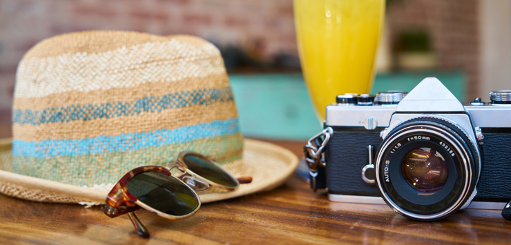 Image of sunglasses, sun hat, camera on table