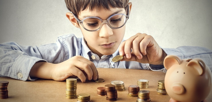 Image of young boy counting money for savings in piggy bank