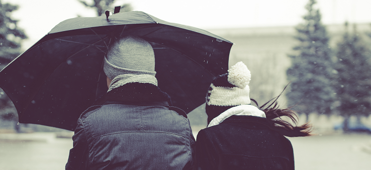Man and woman walking under umbrella