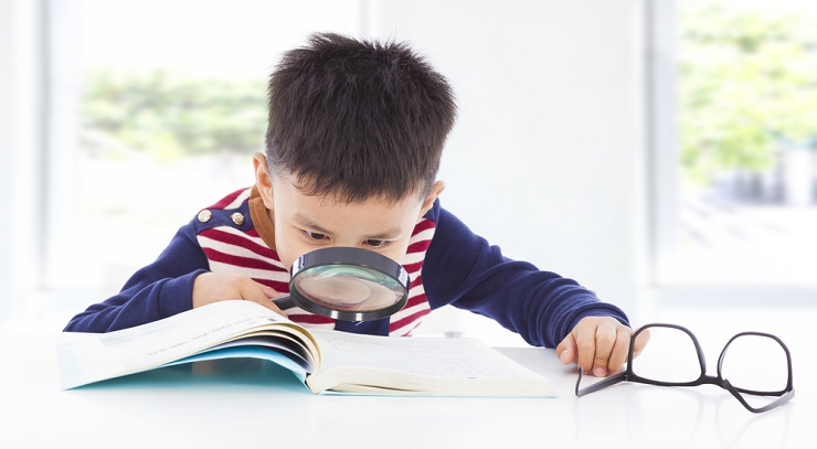 Boy examining text with magnifying glass