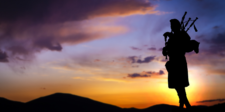 Scottish bagpipe player at sunset