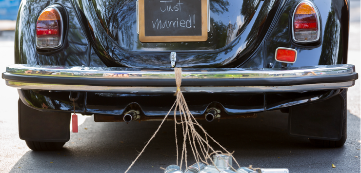 Image of a VW beetle with Jut married sign and tin cans dragging on the ground