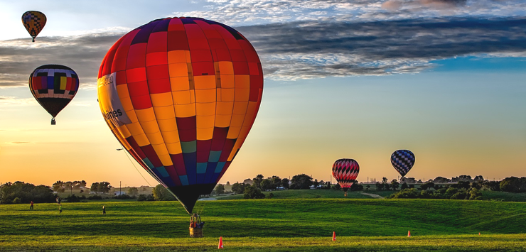 Photo of five hot air balloons floating into distance